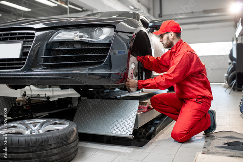 fototapeta na drzwi i meble Auto mechanic in red uniform servicing sports car checking front brakes in the car service