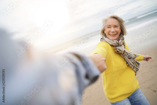 Fotografie, Obraz  Energetic senior woman holding hands with husband in playful manner