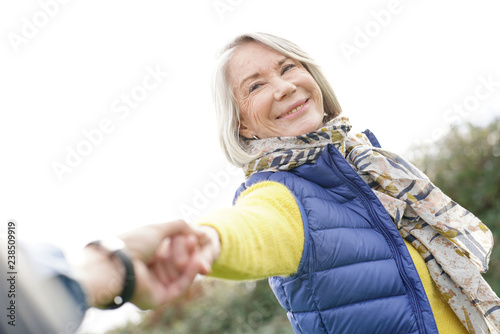 Obraz  Portrait of vibrant senior woman holding partner's hand and pulling him along outdoors - fototapety do salonu