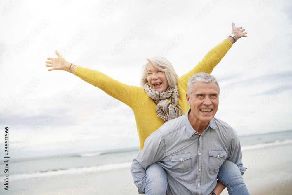 Fototapety, obrazy: Modern vibrant senior couple piggy back riding on beach