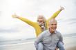 canvas print picture - Modern vibrant senior couple piggy back riding on beach