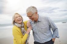 Portrait Of Happy Modern Senior Couple On Beach In Fall