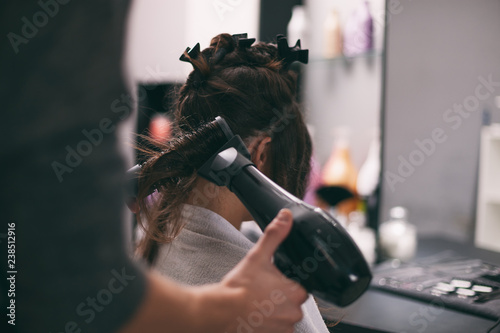 Young woman getting new hairstyle at professional hair styling saloon.