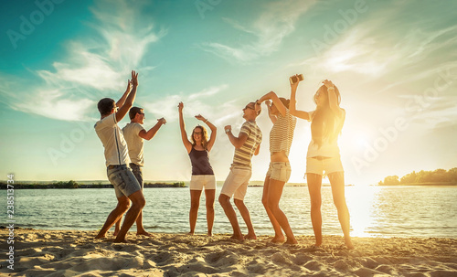 Happiness Friends funny dance on the beach under sunset sunlight