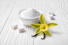 White Granulated And Cubes Sugar With Vanilla Yellow Flower And Sticks
