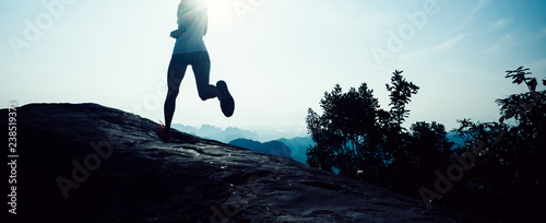 Fotografiet  young fitness woman trail runner running to mountain top