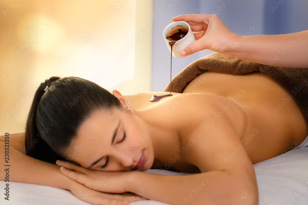 Fototapeta Therapist pouring hot chocolate massage oil on young woman.