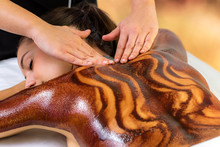 Top View Of Woman Having Hot Chocolate Back Massage .