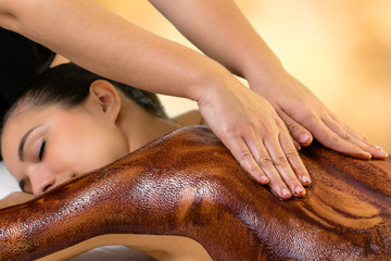 Spa therapist applying curative hot chocolate on woman.