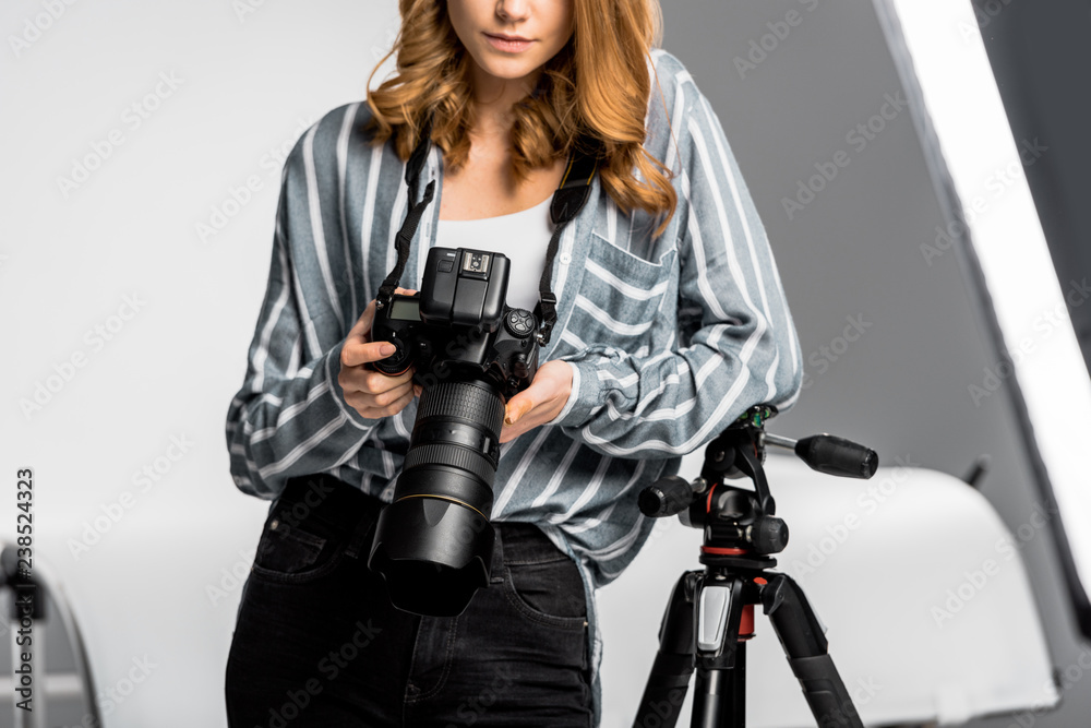 Fototapety, obrazy: cropped shot of beautiful young woman using professional photo camera in studio