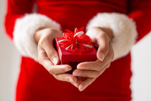 Small Red Present Box With Bow In Female Hands. Woman In Santa Costume Receiving Christmas Gift. Small Gifts Concept