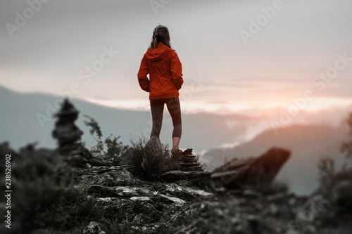 Foto auf Leinwand Schwarz Hiker stands on the cliff and enjoys sunset surrounded by rocks and stacked stones. Altai Republic, Russia