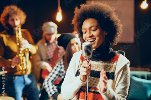 Close up of mixed race woman singing. In background band playing instruments. Home studio interior. - 238540718