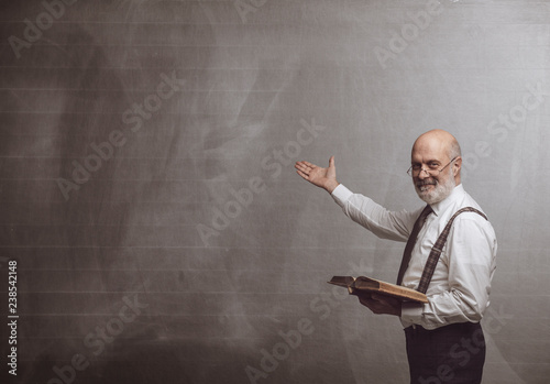 Smiling confident professor teaching and pointing at the blackboard Fototapeta