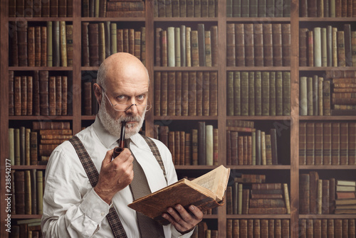 Academic professor in the library holding a book Canvas Print