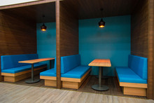 Cozy Blue Sofas Near Table In Popular Cafe. Modern Interior Of Public Establishment With Compartment Walls. Coworking Space Concept