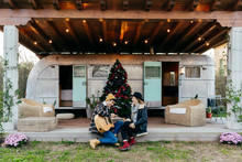 Young Couple With Guitar Near Christmas Tree