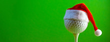 The Golf Ball Mounted On The Tee Is Wearing A Santa Claus Souvenir Hat. Blank For A Postcard For A Golfer To Celebrate The New Year And Christmas. Bright Green Background. Copy Space.
