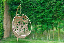 Hanging Bench Seat Chair In Basket Design From Rattan In The Park.