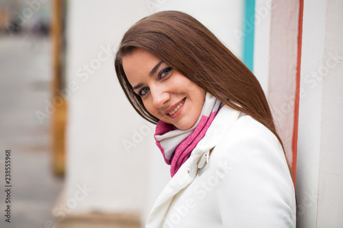 Obraz na plátně  Portrait of a young beautiful woman in white classic coat