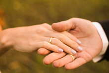 Bridal Couple Holding Hands, Showing Wedding Rings