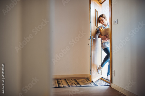 Obraz A young woman with groceries in paper shopping bag walking in through front door. - fototapety do salonu