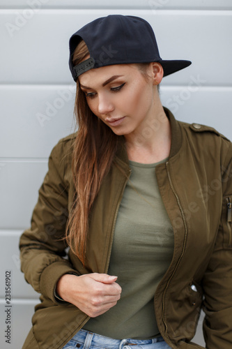 0bd8bb20a5 Sexy beautiful pretty attractive young woman with long brown hair in a  stylish military green jacket in a gray T-shirt and black fashionable  basketball cap, ...