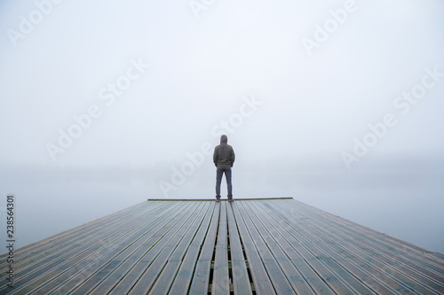Fototapeta Young man standing alone on edge of footbridge and staring at lake
