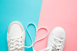 canvas print picture - Heart created from white shoelaces between male and female sport shoes. Love concept. Top view. Empty place for lovely, cute text, quote or sayings on pastel blue and pink paper background. Closeup.