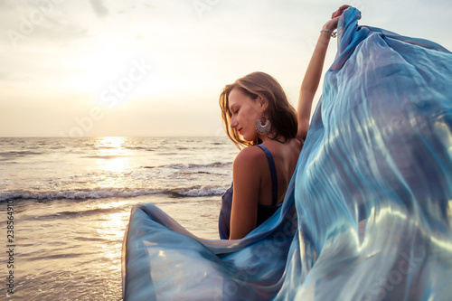 Obraz na plátně  Beautiful brunette girl in blue gray chameleon dress with long train sitting on a beach at amazing sunset