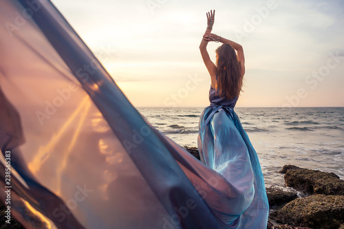 Fotografia Beautiful brunette girl in blue gray chameleon dress with long train sitting on a beach at amazing sunset