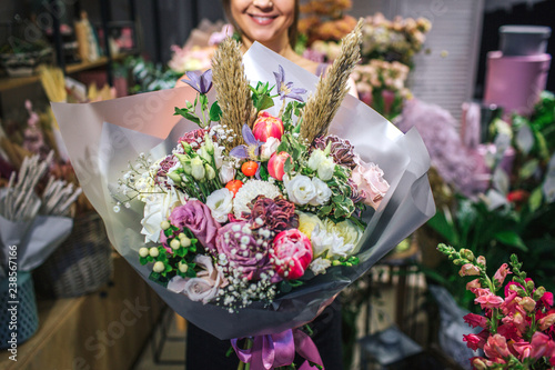 Nice and colorful bouqette of different flowers. Female florist hold it and smile. She is in flower shop. Cut view. Close up.