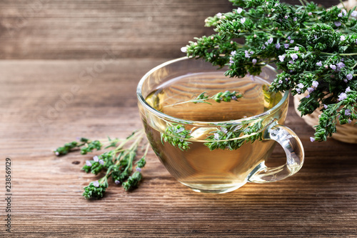 Fototapeta Herbal tea with thyme over rustic wooden background. obraz