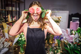 Fototapeta Kwiaty - Funny and positive young female florist cover eyes with roses and show tongue. She has fun. Plants and flowers stand in vases behind.