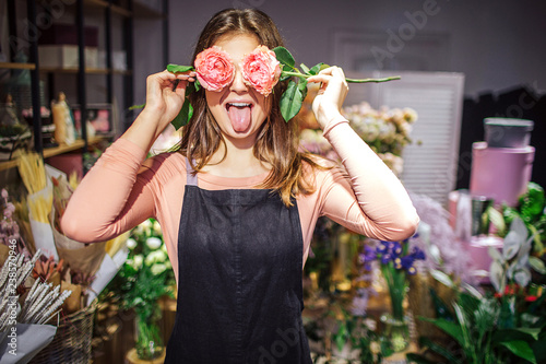 Cadres-photo bureau Fleuriste Funny and positive young female florist cover eyes with roses and show tongue. She has fun. Plants and flowers stand in vases behind.