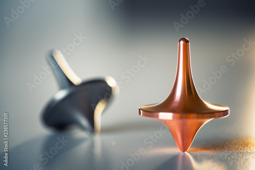 Fotografie, Obraz Two totem spinning tops spinning, wobbling and stopping