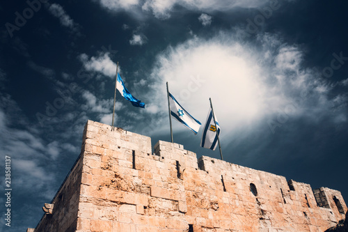 Photo Israel and Jerusalem flags on Jerusalem old city walls against the blue sky with