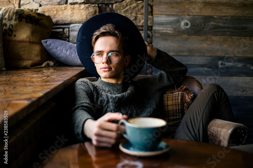 Fotografie, Obraz  Young handsome guy in a black hat and glasses drinking coffee in a cozy cafe