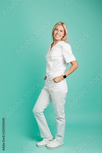 Fotografie, Obraz  Beautiful female doctor standing at full height on a green background