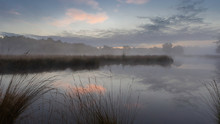 Serene Misty Sunrise With Blue Sky And Orange Cloud And Trees Reflecting In The Water Of A Fen At The Hatertse Vennen, Nijmegen, Netherlands