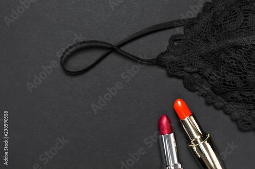 Valokuva  Black lace bra underwear, red lipstick on dark background top view flat lay