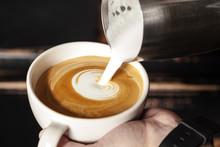 A Professional Barista Holds A Cup Of Coffee, Making A Beautiful Heart Shape Latte Art. Hot Art Latte Coffee With Heart Shape In White Cup