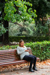 Pregnant attractive woman with smartphone sitting on bench