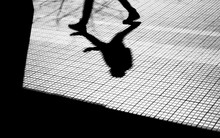 Blurry Silhouette And Shadow Of A Person On A City Sidewalk