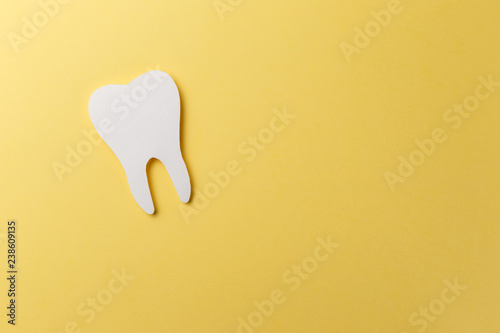 Fotomural White tooth on yellow background with copy space