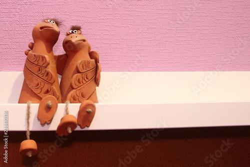Fotografie, Obraz  Two embracing funny birds sitting on a shelf - ceramic statuette on white pink b