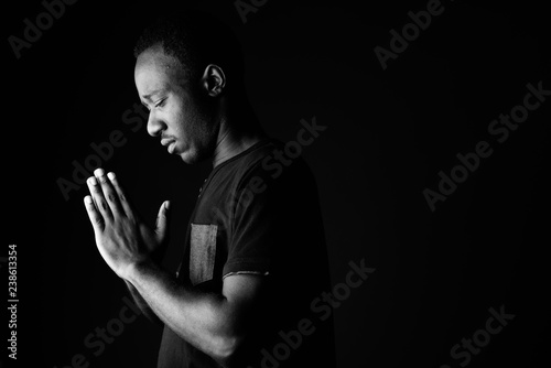 Fotografie, Obraz Sad young African man praying in black and white
