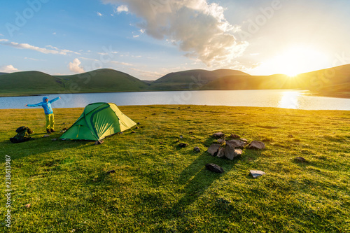 Canvas Prints Camping Girl camping wild in tent by Akna lake on sunrise, Geghama volcano mountains, Armenia