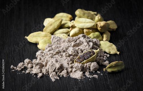 Fototapeta spices; cardamom pods and ground coffee on a dark background obraz