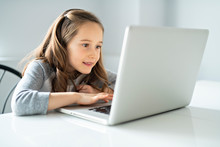 A Young Girl Using Laptop At Home